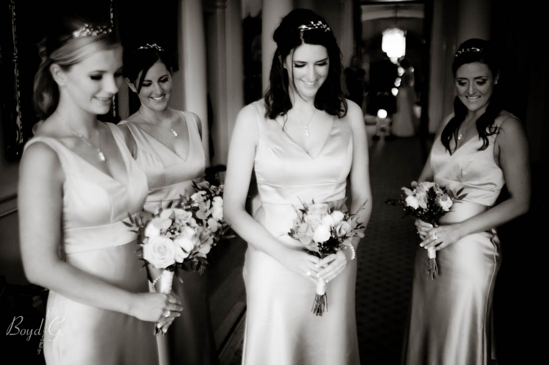 A beautiful moment where the bridesmaids look adoringly down at the flower girl.