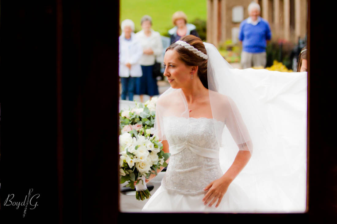 Bride is framed in by the door as she waits to enter the church as onlookers gaze at her in her beautiful gown.