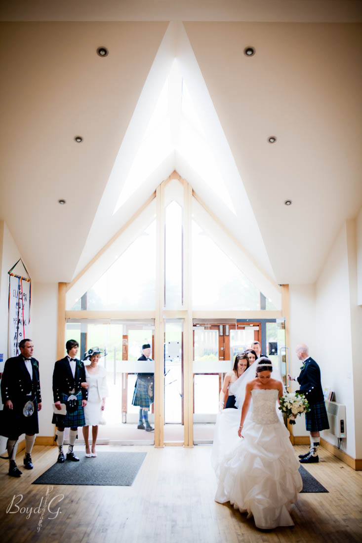 Bride walks into a church with modern architecture and gets ready to walk down the aisle to be married.