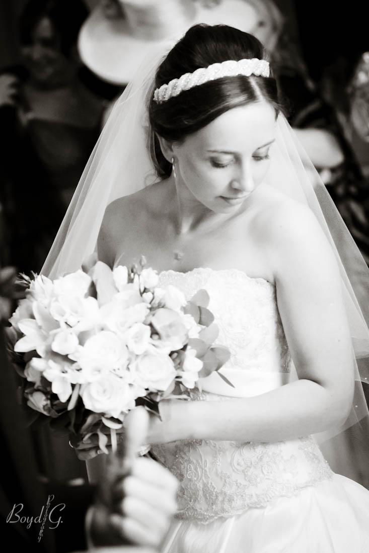 The lovely bride elegantly looks down at her feet in a crowd of people.